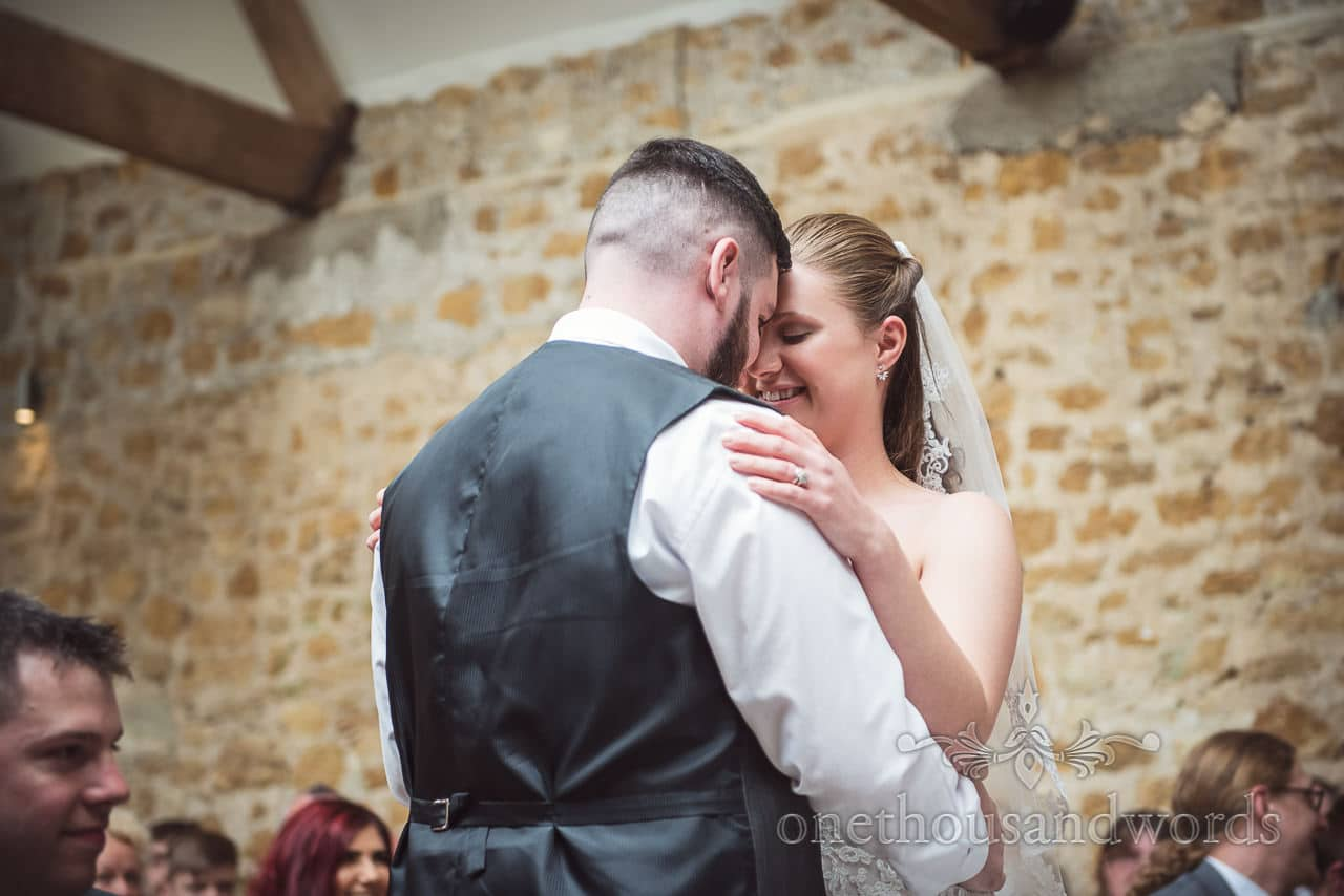 Bride and groom embrace during ceremony at Tithe Barn Symondsbury Wedding
