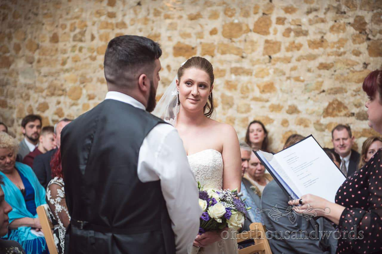 Bride and groom exchange looks during ceremony at Tithe Barn Symondsbury Wedding