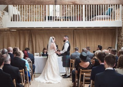 Bride and groom exchange their promises during ceremony at Tithe Barn Symondsbury Wedding