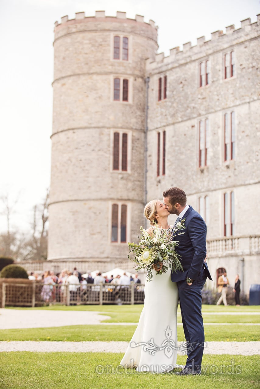 Bride and groom kiss in front of Lulworth Castle Wedding venue in Dorset