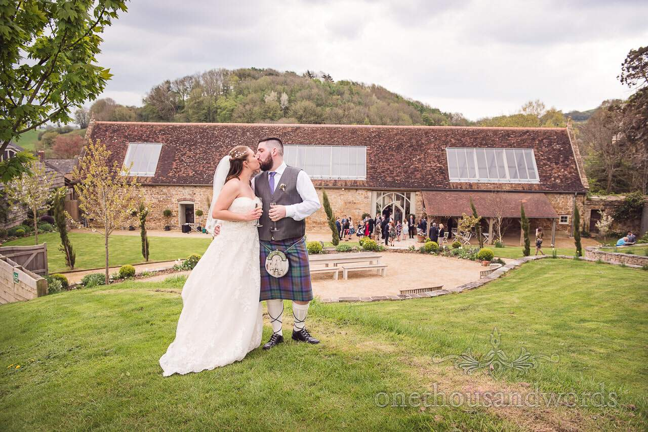Bride and groom kiss in garden during Tithe Barn Symondsbury Wedding