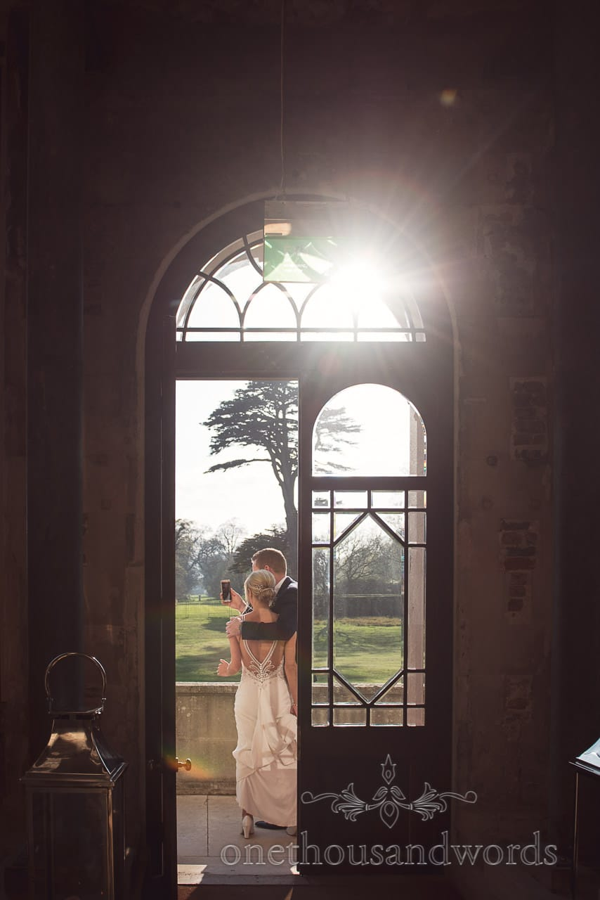 Bride and groom make face time call with sunburst at Lulworth Castle Wedding