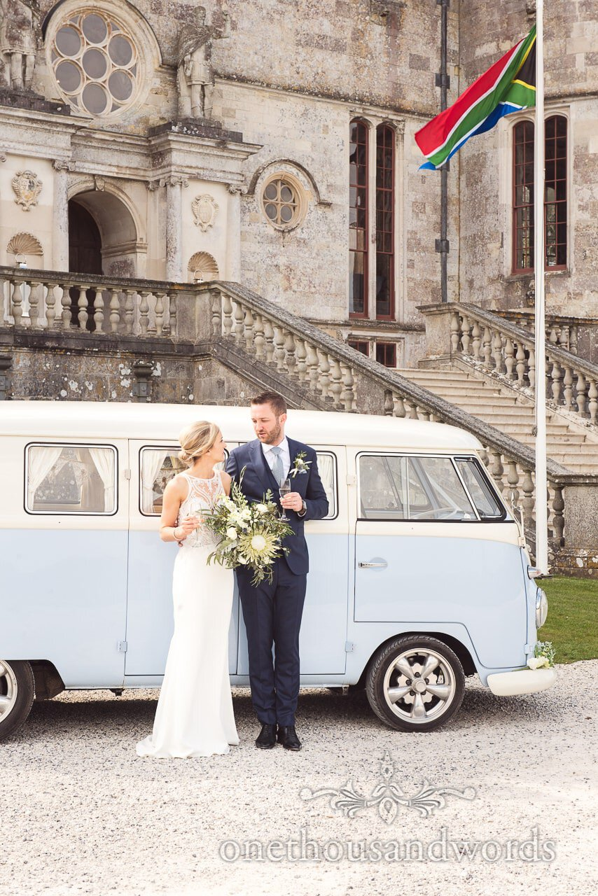 Bride and groom with VW van and South African Flag at Lulworth Castle Wedding