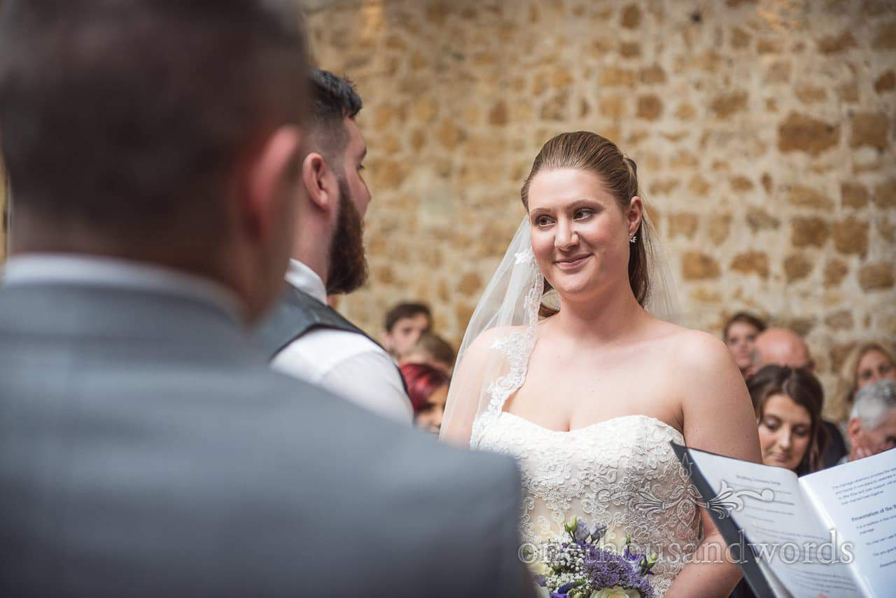 Bride looks at groom during ceremony at Tithe Barn Symondsbury Wedding