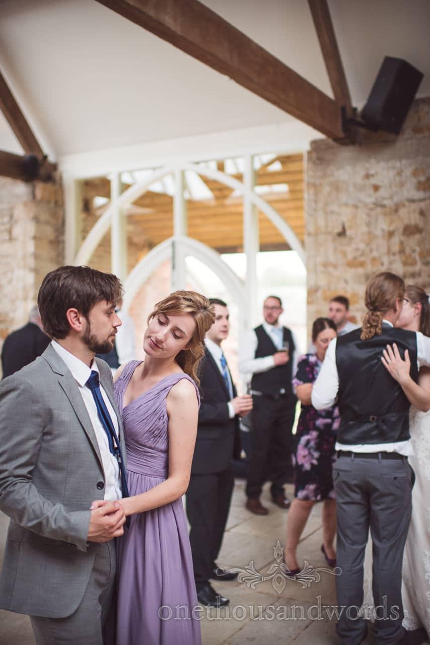 Bridesmaid dances with partner during Tithe Barn Symondsbury Wedding