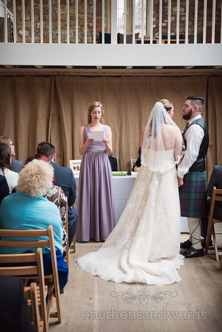 Bridesmaid delivers reading during ceremony at Tithe Barn Symondsbury Wedding