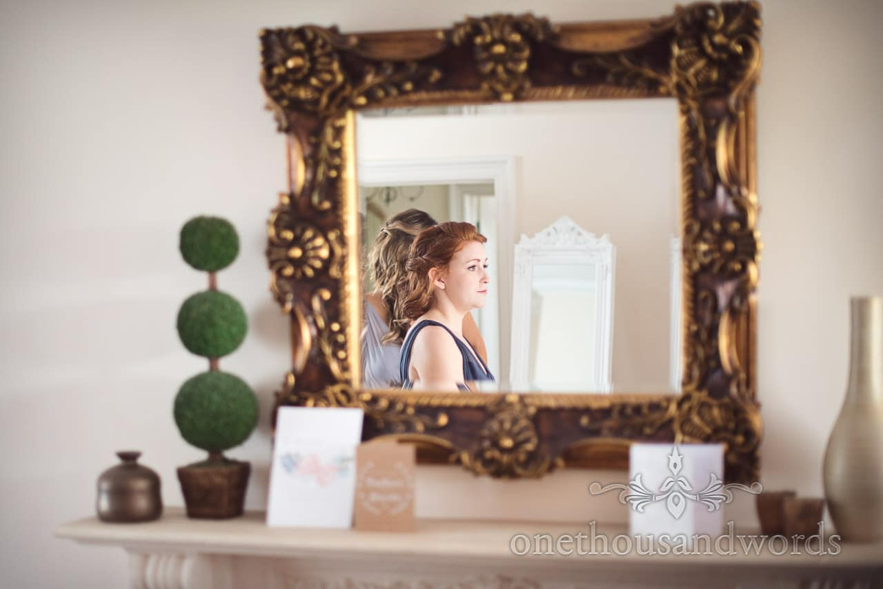 Bridesmaid in mirror during morning of Lulworth Castle Wedding Photos