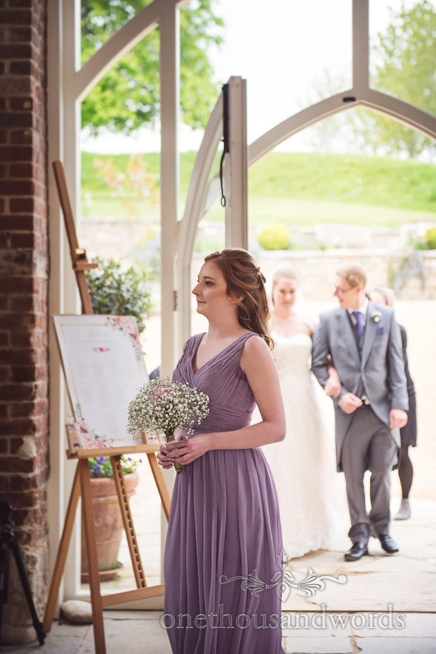 Bridesmaid in pale purple dress leads bride in at Tithe Barn Symondsbury Wedding