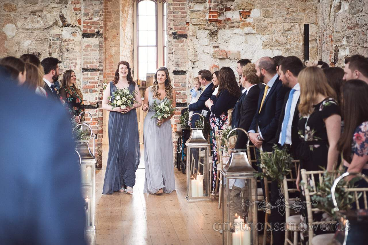 Bridesmaids in green and mint bridesmaid dresses enter Lulworth Castle Wedding