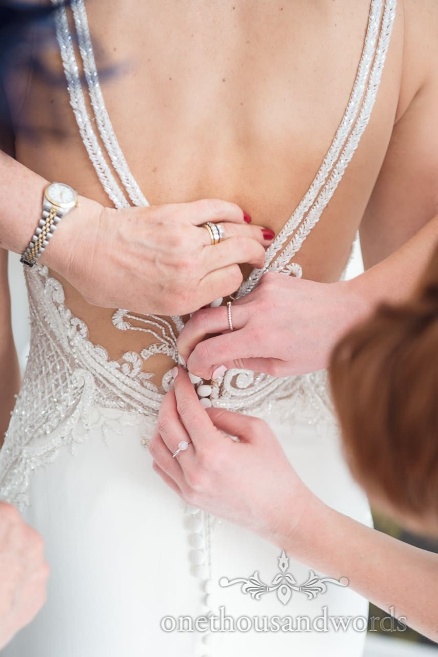 Buttons on brides dress are fastened from Lulworth Castle Wedding Photos