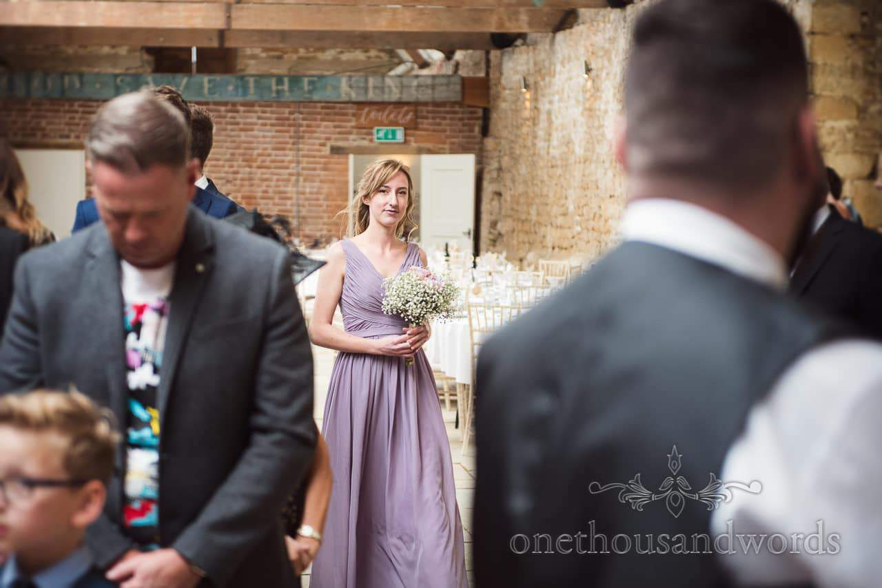 First bridesmaid in pale purple dress leads bride in at Tithe Barn Symondsbury Wedding