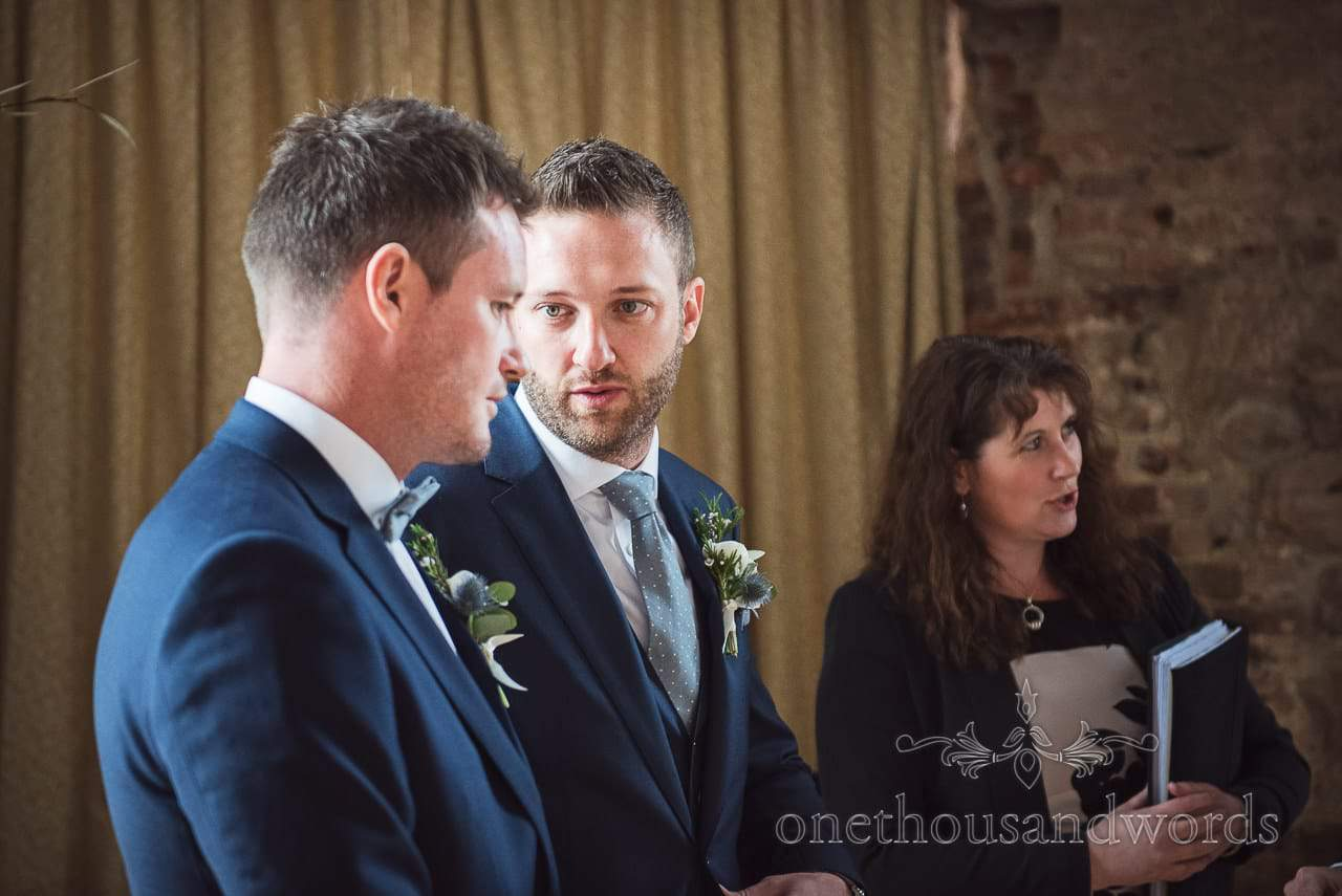 Groom and grooms man in blue wedding suits wait for Lulworth Castle Wedding