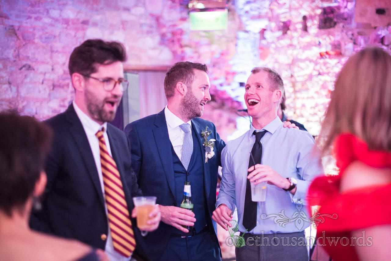 Groom and wedding guests laughing on dance floor at Lulworth Castle wedding