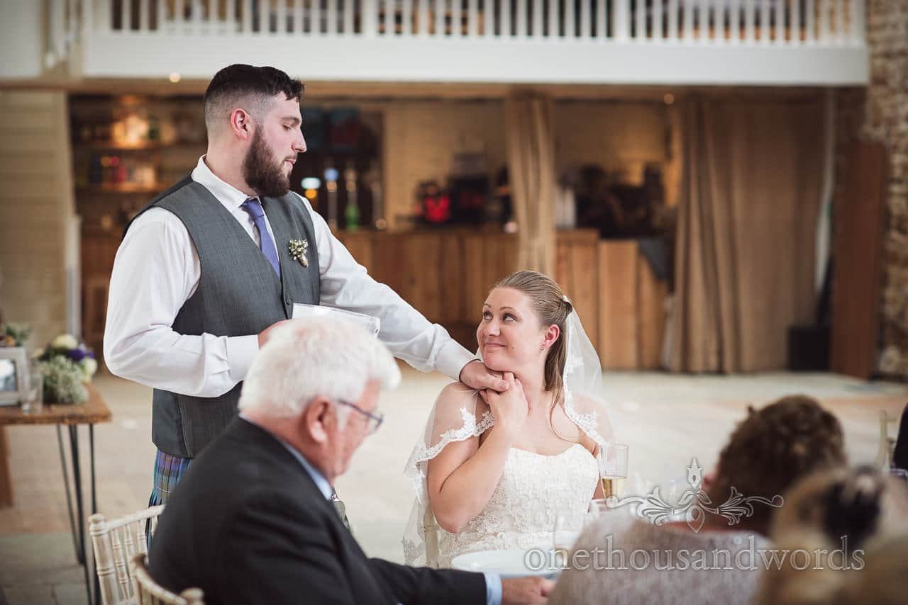 Groom holds hand of his wife as he delivers speech at Tithe Barn Symondsbury Wedding