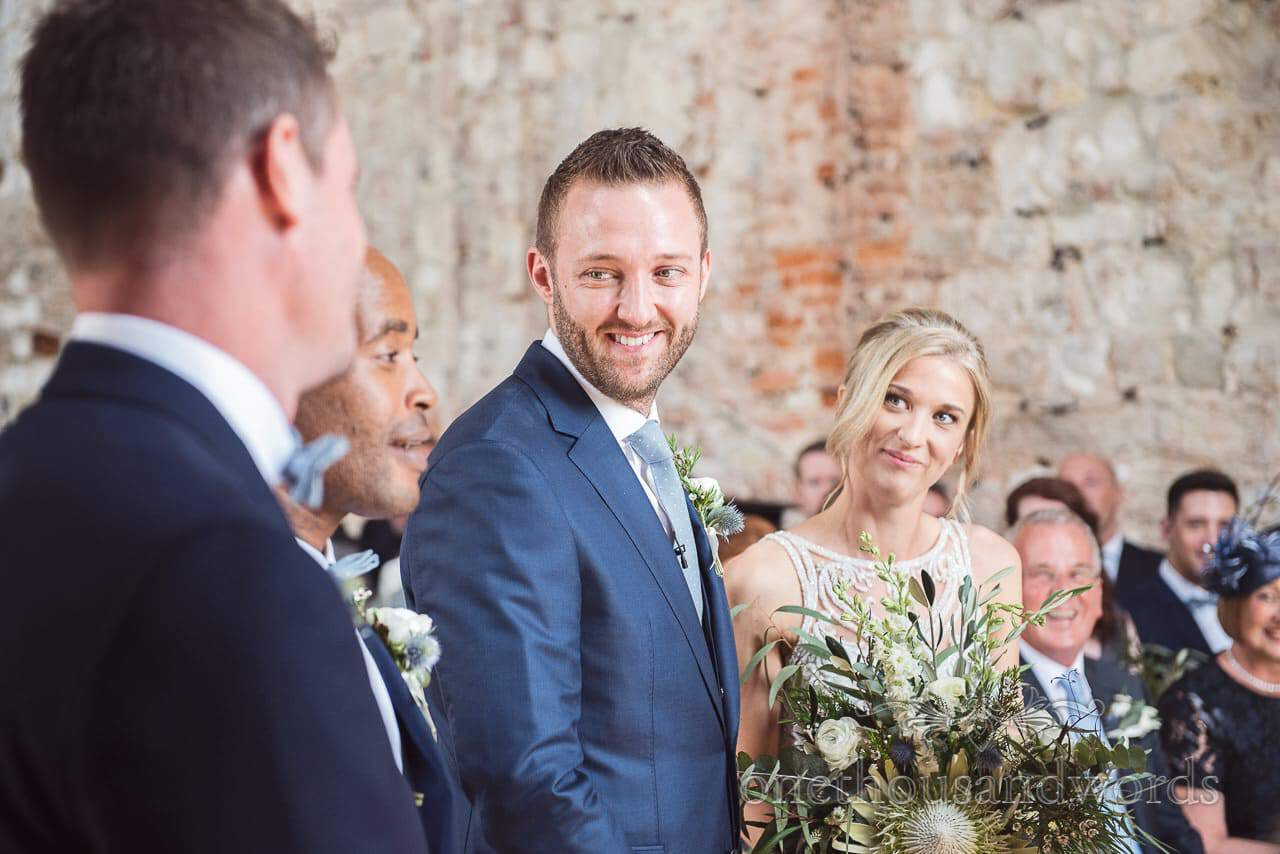 Groom in blue suit looks at best men during Lulworth Castle Wedding ceremony