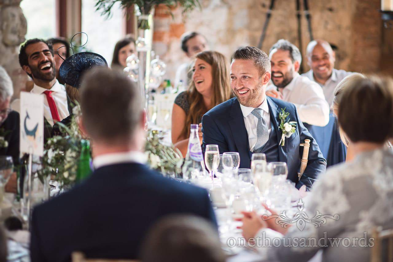 Groom laughs at wedding speeches at Lulworth Castle Wedding venue in Dorset