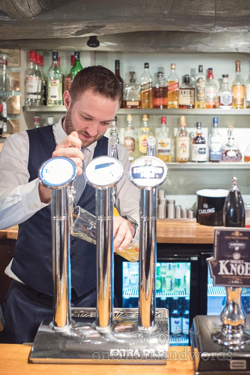 Groom pulls his own pint before Lulworth Castle Wedding Photos