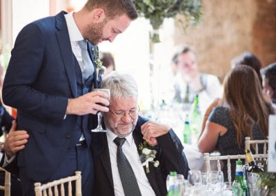 Groom shares a moment with his father at Lulworth Castle Wedding in Dorset