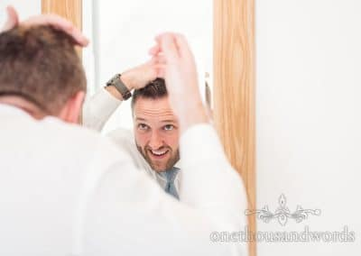 Groom styles hair on morning of Lulworth Castle Wedding Photos