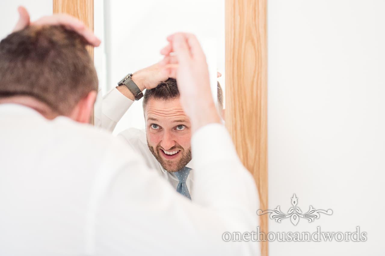 Groom styles hair on morning of Lulworth Castle Wedding Photos