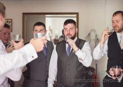 Groomsman and groom raise toast before Tithe Barn Symondsbury Wedding
