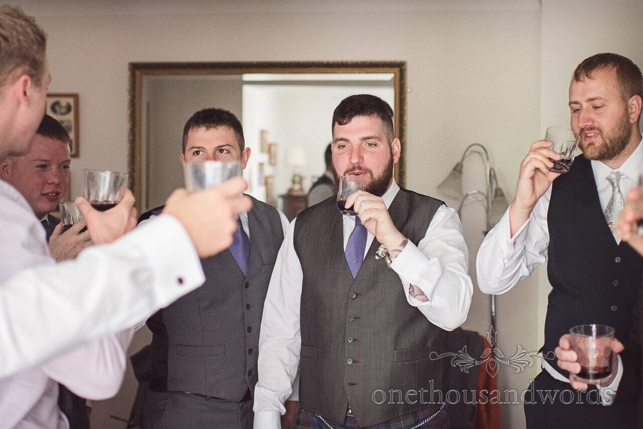 Groomsman and groom raise toast before Tithe Barn Symondsbury Wedding