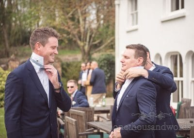 Groomsmen adjust bow ties on morning of Lulworth Castle Wedding Photos