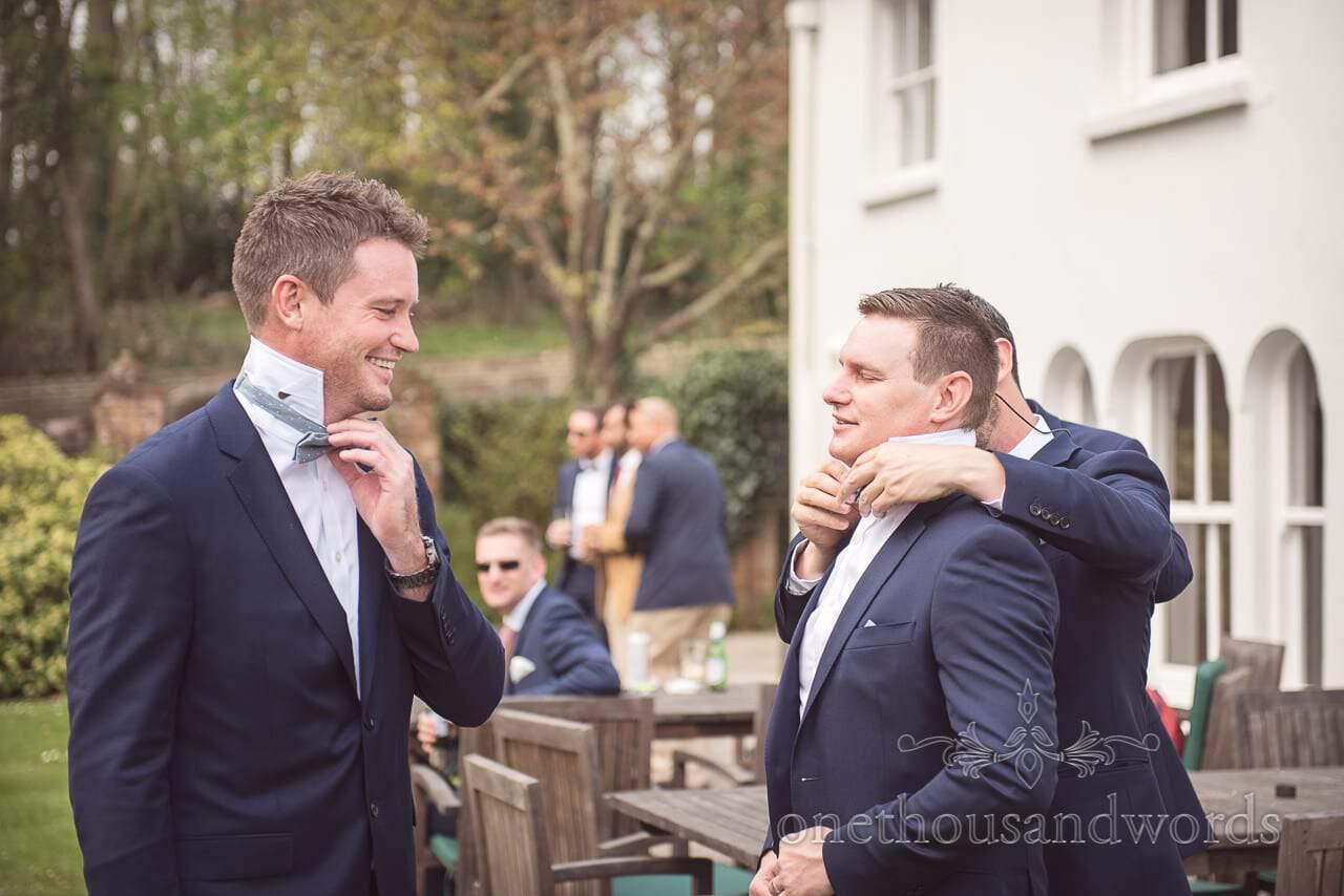 Groomsmen adjust bow ties on morning of Lulworth Castle Wedding Photos