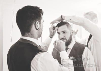 Groomsmen help groom with hair styling before Tithe Barn Symondsbury Wedding
