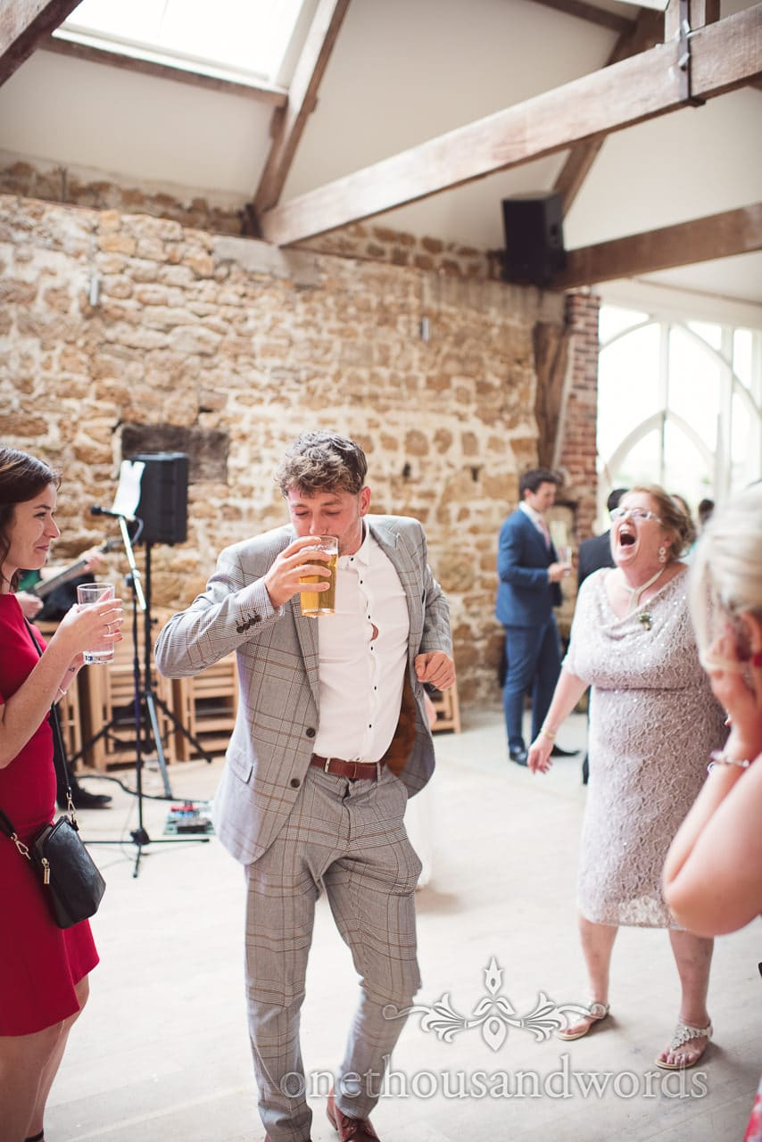 Guest drinking and dancing on the dance floor at Tithe Barn Symondsbury Wedding