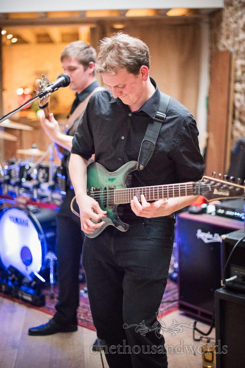 Guitarist plays during Tithe Barn Symondsbury Wedding