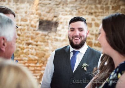 Laughing groom before Tithe Barn Symondsbury Wedding