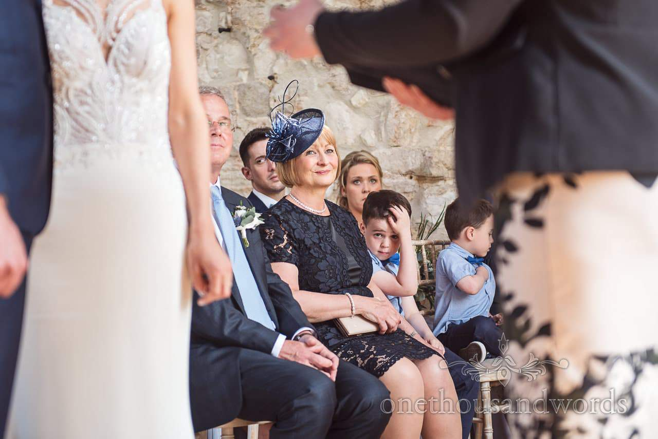 Mother of the bride smiles during Lulworth Castle Wedding ceremony photos