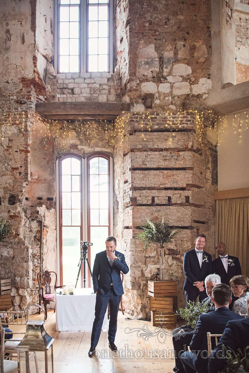 Nervous groom awaits his bride at Lulworth Castle Wedding ceremony in ruined castle