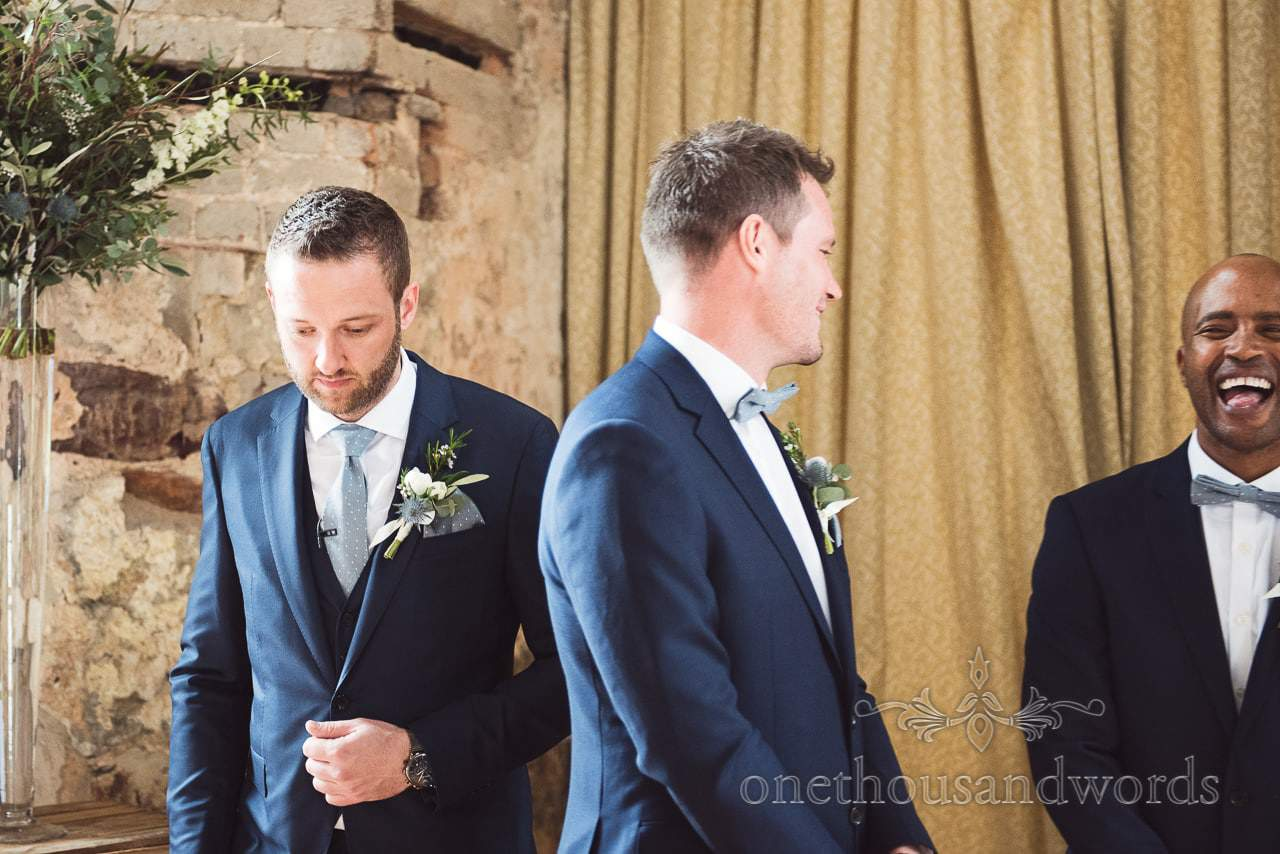 Nervous looking groom with laughing groomsmen at Lulworth Castle Wedding