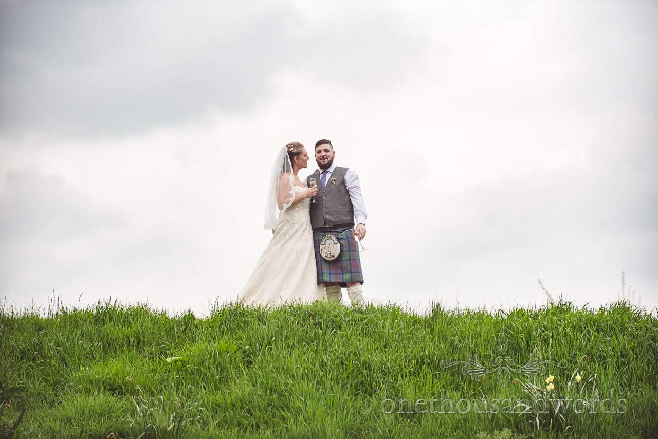 Newlyweds on top of bank in garden at Tithe Barn Symondsbury Wedding