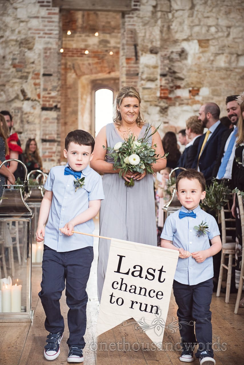 "Page boys with ""Last Chance to Run"" sign enter Lulworth Castle Wedding ceremony"
