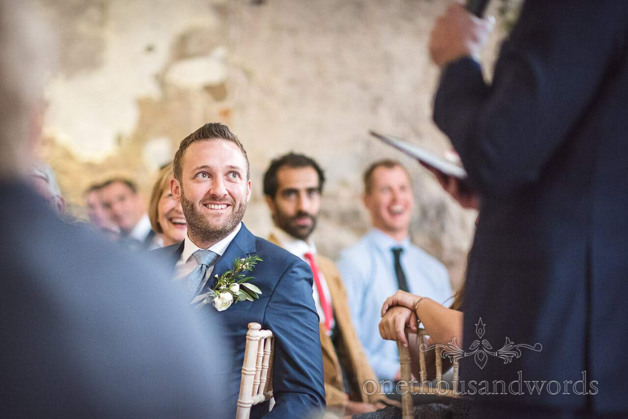 Photograph of groom watching best man's speech at Lulworth Castle Wedding