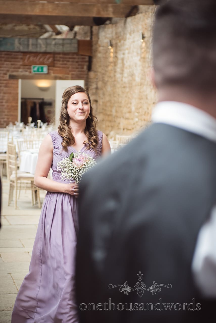 Second bridesmaid in pale purple dress leads bride in at Tithe Barn Symondsbury Wedding
