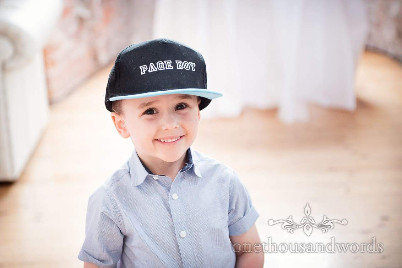 Smiling page boy wears page boy baseball cap at Lulworth Castle Wedding