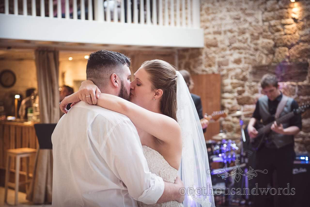 The bride and groom kiss during first dance at the Tithe Barn Symondsbury Wedding
