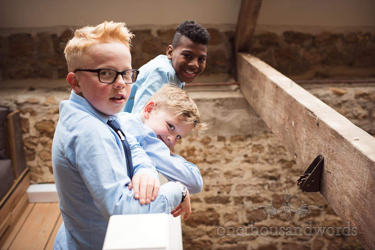 Three young guest look on during first dance at the Tithe Barn Symondsbury Wedding