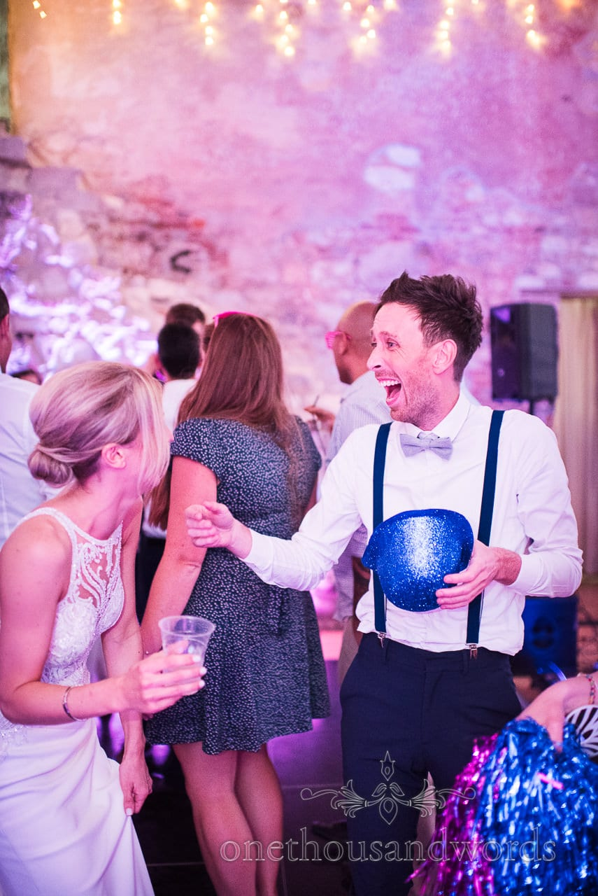 Wedding guest laughing with sparkly bowler hat fancy dress dancing