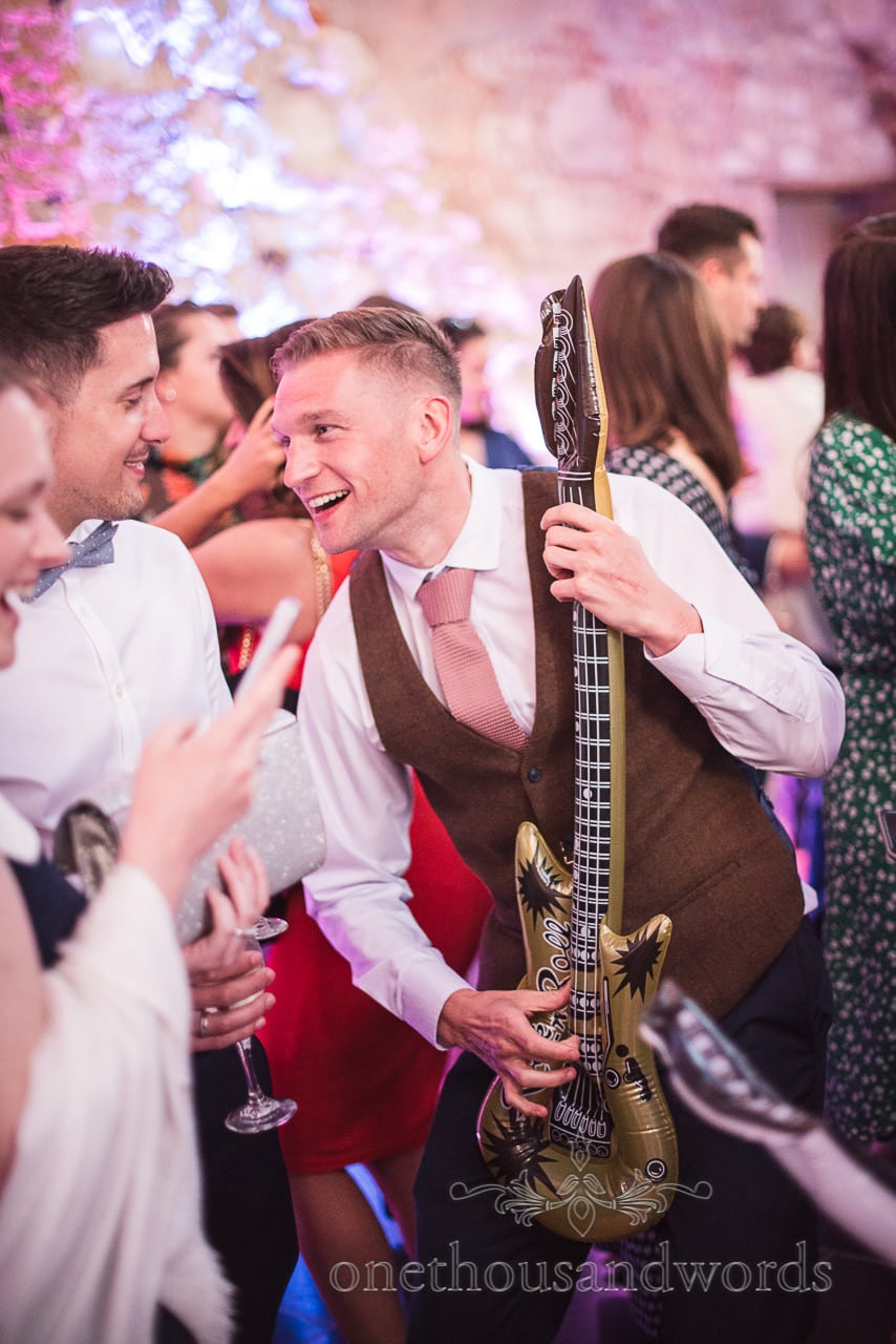 Wedding guest plays inflatable guitar on dance floor at Lulworth Castle Wedding