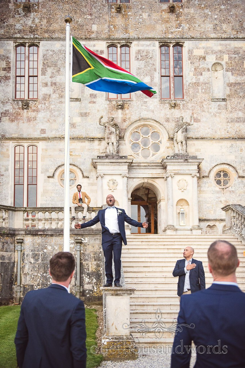 Wedding guest sing to the South African Flag at Lulworth Castle Wedding Photos