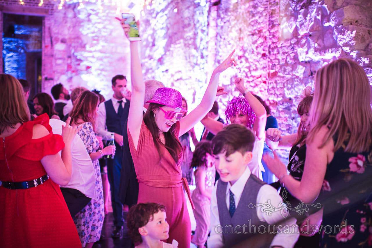 Wedding guests in fancy dress dancing at Lulworth Castle wedding photos