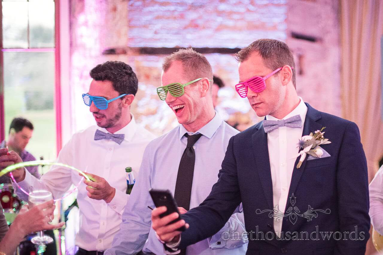 Wedding guests in matching coloured fancy dress glasses at Lulworth castle wedding