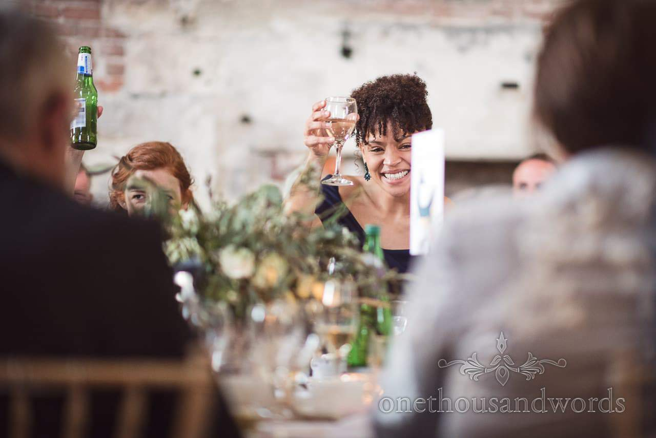 Wedding guests raise a toast dung speeches at Lulworth Castle Wedding