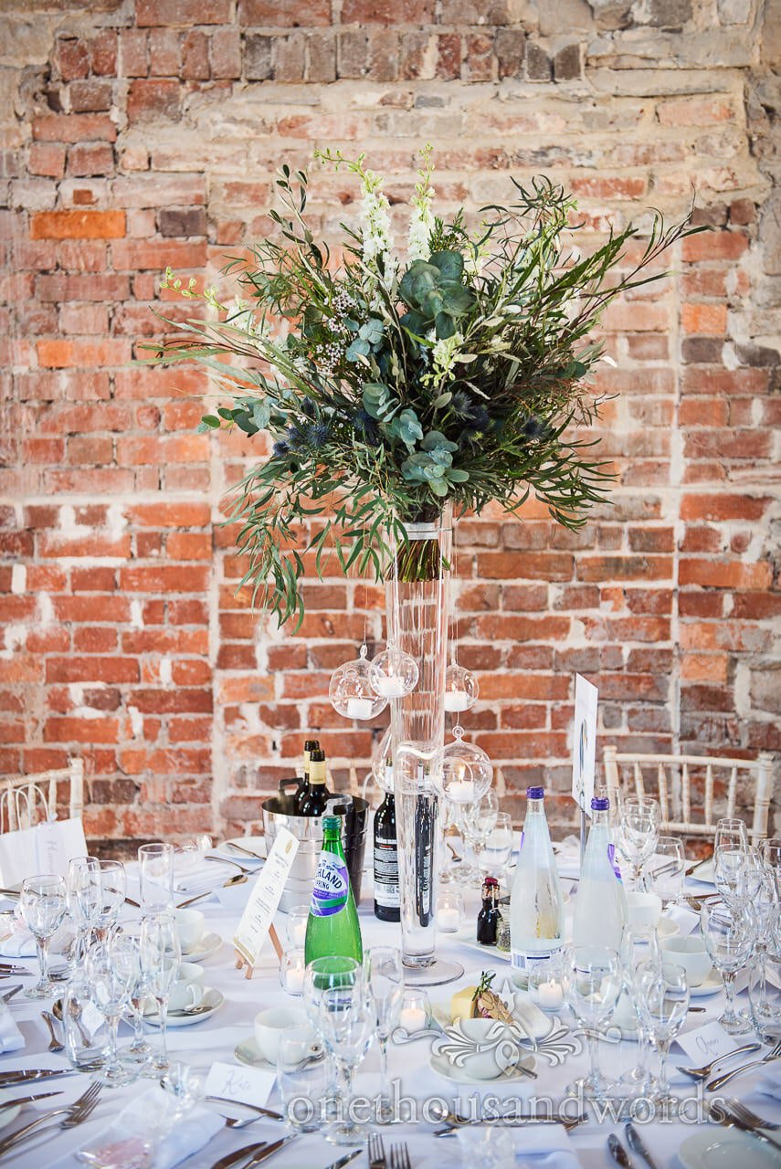 Wedding table spray of White flowers with green foliage against red brick Castle walls