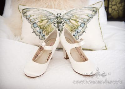 White wedding shoes with butterfly cushion from Lulworth Castle Wedding Photos